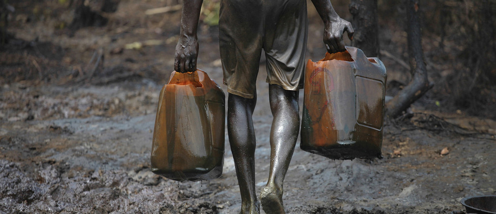 A man works at an illegal oil refinery site near river Nun in Nigeria's oil state of Bayelsa November 27, 2012.