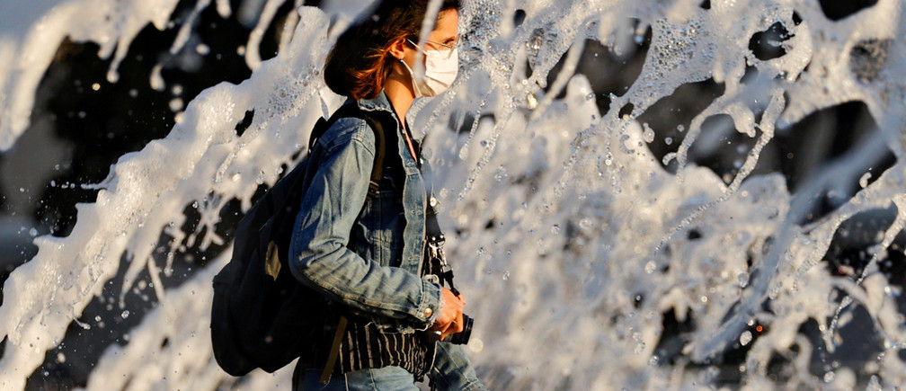 A woman wearing a face mask walks past a fountain amid the spread of the coronavirus disease (COVID-19), in San Diego, California, U.S., June 18, 2020. REUTERS/Mike Blake     TPX IMAGES OF THE DAY - RC22CH94JQX4