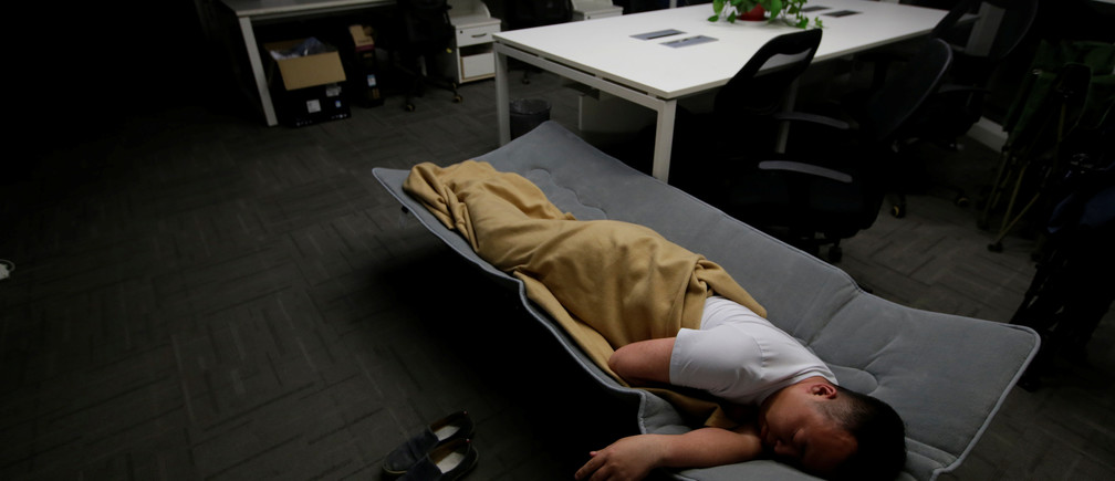 """Ma Zhenguo, a system engineer at RenRen Credit Management Co., sleeps on a camp bed at the office after finishing work early morning, in Beijing, China, April 27, 2016. Office workers sleeping on the job is a common sight in China, where a surplus of cheap labour can lead to downtime at work. But in China's technology sector, where business is growing faster than many start-up firms can hire new staff, workers burn the midnight oil to meet deadlines and compete with their rivals. Some companies provide sleeping areas and beds for workers to rest during late nights. REUTERS/Jason Lee       SEARCH """"JASON SLEEP"""" FOR THIS STORY. SEARCH """"THE WIDER IMAGE"""" FOR ALL STORIES  TPX IMAGES OF THE DAY - S1BETDIDEDAA"""