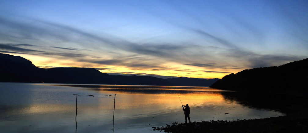 A man casts his fishing line in Bals-Fiord, north of the Arctic Circle, near the village of Mestervik in northern Norway September 30, 2014. REUTERS/Yannis Behrakis (NORWAY - Tags: ENVIRONMENT TRAVEL) - GM1EAA108Y301