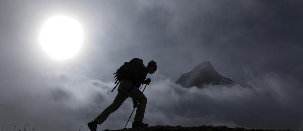 A hiker walks past the Matterhorn mountain at sunrise in the Swiss Alps near Zermatt September 11, 2013.