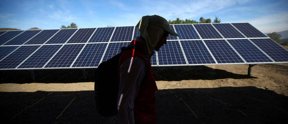 A worker walks past solar panels at a solar plant near Santiago, Chile May 5, 2017. Picture taken May 5, 2017. REUTERS/Ivan Alvarado - RC1D3E2E4110