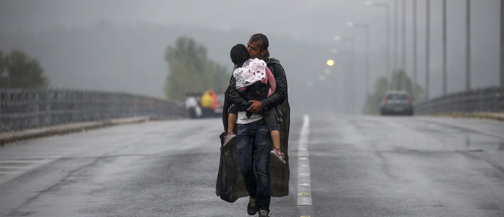 A Syrian refugee kisses his daughter as he walks through a rainstorm towards Greece's border with Macedonia, near the Greek village of Idomeni, September 10, 2015. Reuters and The New York Times shared the Pulitzer Prize for breaking news photography for images of the migrant crisis in Europe and the Middle East.  REUTERS/Yannis Behrakis      TPX IMAGES OF THE DAY - RTX2AJJE