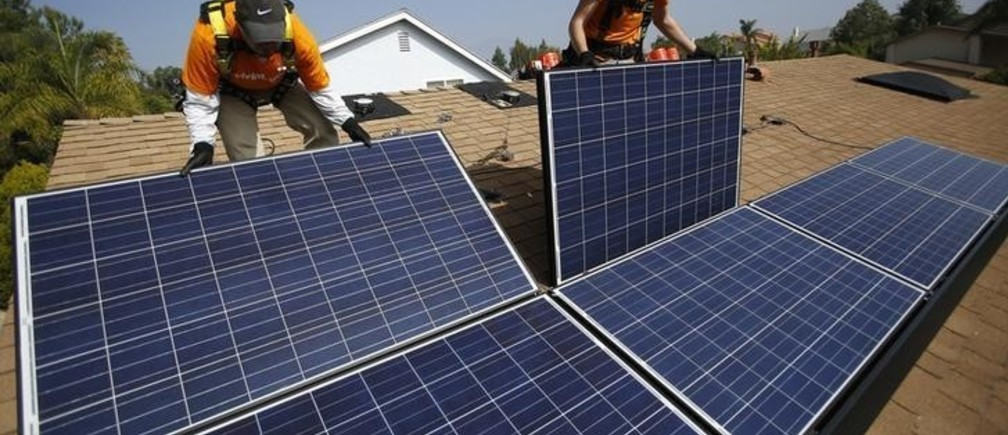 Vivint Solar technicians Eduardo Aguilar (L) and Ian Boshard install solar panels on the roof of a house in Mission Viejo, California October 25, 2013.  REUTERS/Mario Anzuoni  (UNITED STATES - Tags: ENERGY)