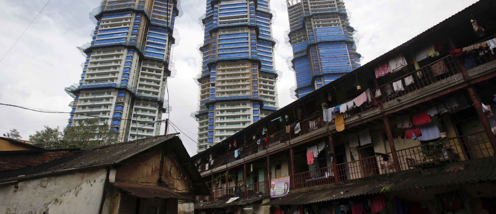 High-rise residential towers under construction are pictured behind an old residential building in central Mumbai September 9, 2011.  REUTERS/Vivek Prakash