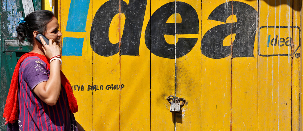 A woman speaks on her mobile phone as she walks past a shop displaying the Idea Cellular Ltd's logo on its shutter in Kolkata, India, November 13, 2017. REUTERS/Rupak De Chowdhuri - RC12D4B825A0