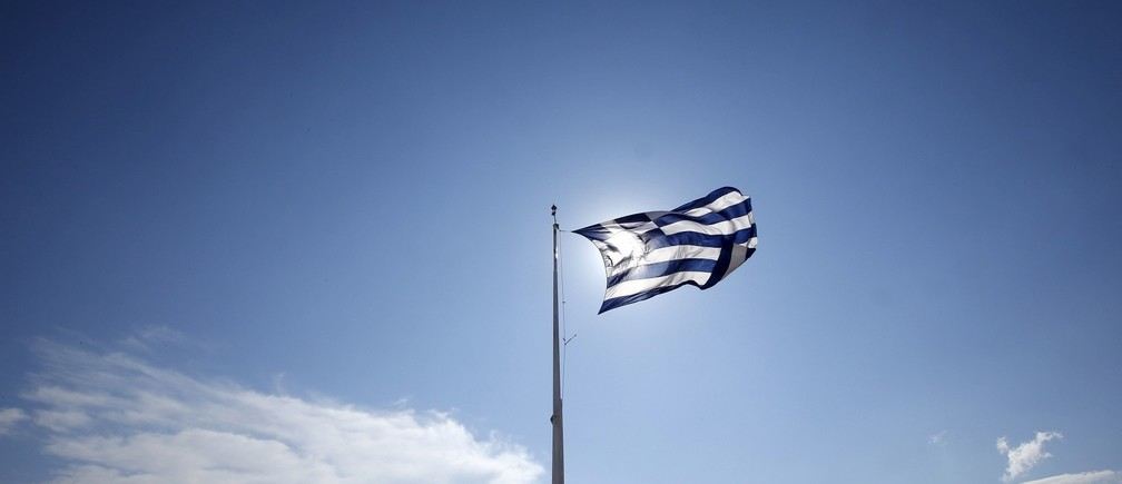 A Greek flag flutters as tourists visit the Acropolis hill archaeological site in Athens, Greece, July 2, 2015. Prime Minister Alexis Tsipras called on Greeks to vote 'no' in Sunday's referendum on a bailout package offered by creditors, in a defiant address that dispelled speculation he was rowing back on the plan under mounting pressure