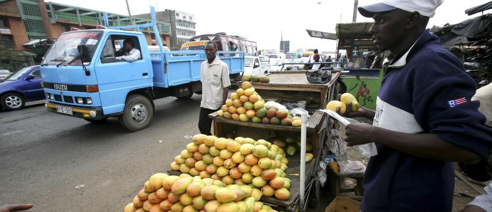 A trader sells mangoes next to moving traffic in Kenya's capital Nairobi, April 3, 2009.