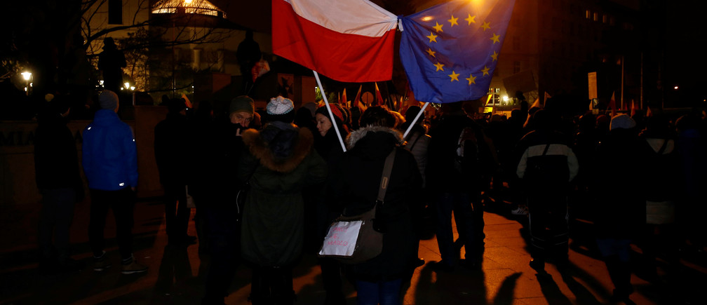 Demonstrators hold Polish and EU flags during a protest outside the Parliament building in Warsaw, Poland December 17, 2016. REUTERS/Kacper Pempel - RTX2VG8M