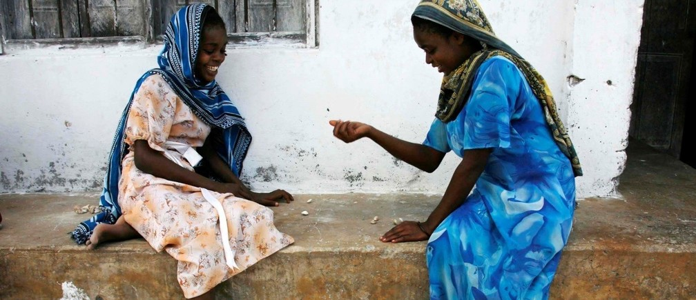 Girls play a game involving the picking up small stones in the village of Bwejuu on Zanzibar island, Tanzania