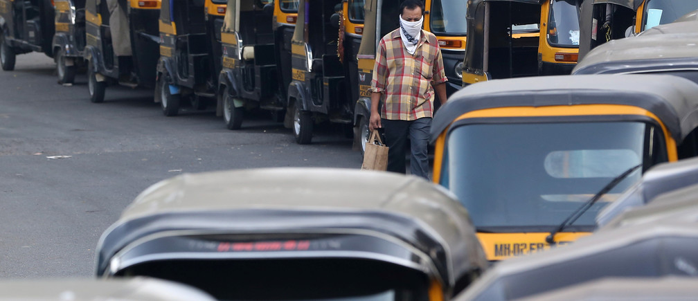A man wearing a handkerchief as a mask moves past parked autorickshaw during a curfew to limit the spreading of coronavirus disease (COVID-19), in Mumbai, India, March 24, 2020. REUTERS/Prashant Waydande - RC29QF9NTAXU