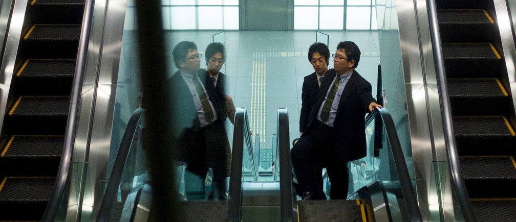 Businessmen ride up on an escalator at a subway station in a banking district in central Tokyo November 27, 2014. Japan's jobless rate fell and the availability of jobs edged higher in October from the previous month, government data released on Friday showed. Picture taken November 27, 2014. REUTERS/Thomas Peter (JAPAN - Tags: BUSINESS EMPLOYMENT) - RTR4FW48
