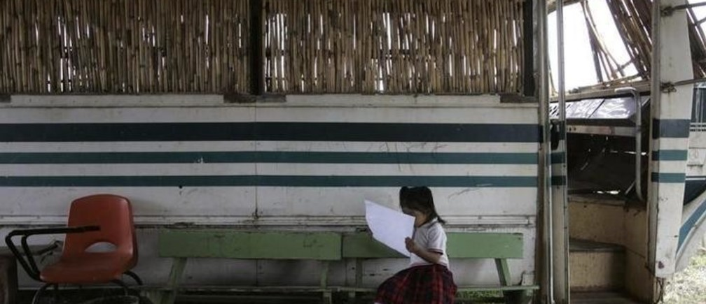"A girl from the ""Insurgentes de la Paz"" (Peace Insurgents) school reads outside an old bus turned into a classroom in the settlement of Pueblo Nuevo, Oaxaca September 1, 2009. The bus was donated to the neighborhood by a truck company after the other classrooms became too small for the 83 children at the school. Mexico, ridden with organized crime and drug gang violence, ranks poorly in education standards, which is holding back the country's economic growth and development according to analysts. Picture taken September 1, 2009. REUTERS/Jorge Luis Plata (MEXICO POLITICS EDUCATION SOCIETY IMAGES OF THE DAY)"