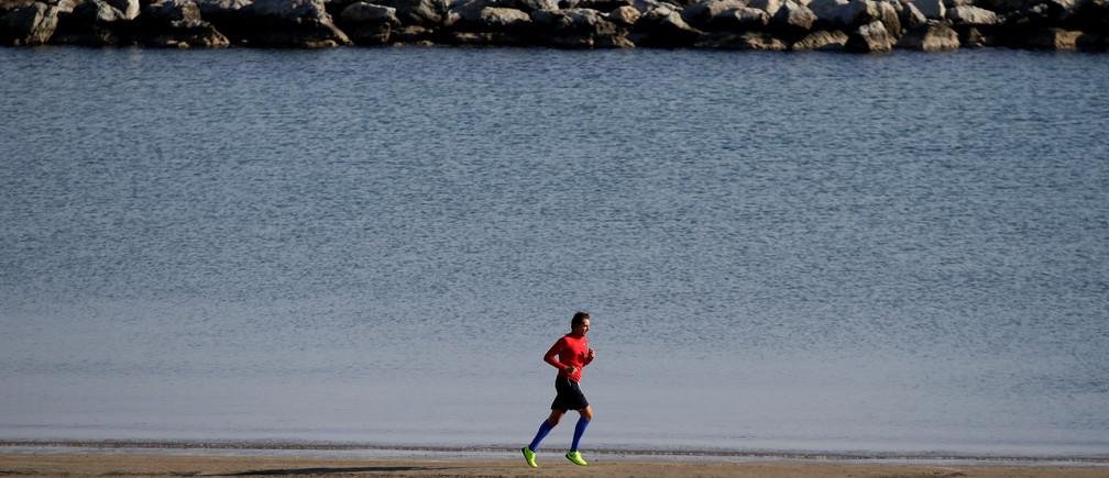 A man runs along the beach in Rimini, Italy, September 23, 2017.       REUTERS/Max Rossi - RC14E55D6BA0