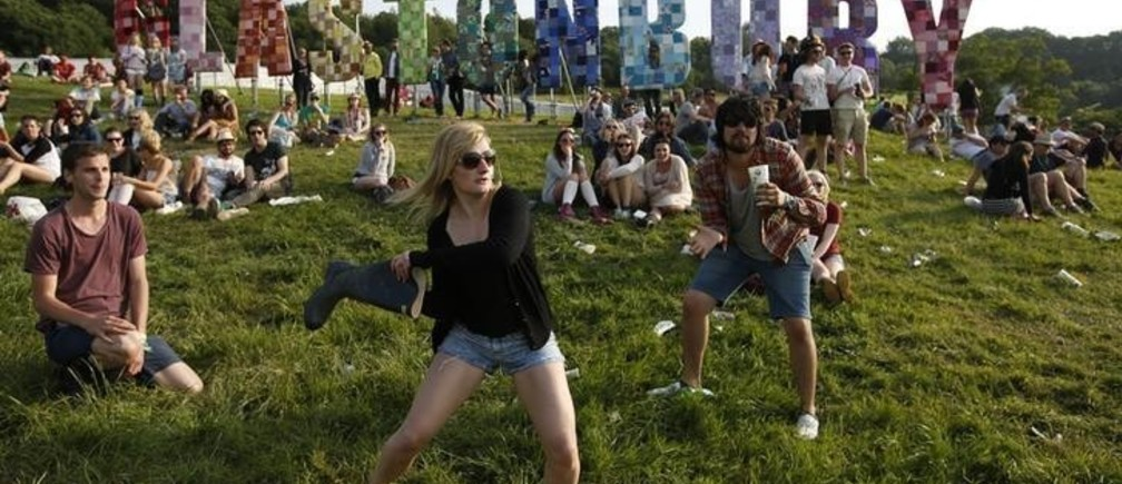Festival goers play baseball, batting a beer can with a wellington boot, on the first day of Glastonbury music festival at Worthy Farm in Somerset, June 27, 2013. REUTERS/Olivia Harris (BRITAIN)