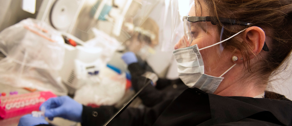 Kylene Karnuth, a clinical lab scientist, works with coronavirus samples as researchers begin a trial to see whether malaria treatment hydroxychloroquine can prevent or reduce the severity of the coronavirus disease (COVID-19), at the University of Minnesota in Minneapolis, Minnesota, U.S. March 19, 2020.  REUTERS/Craig Lassig - RC2ANF9Z4NVV