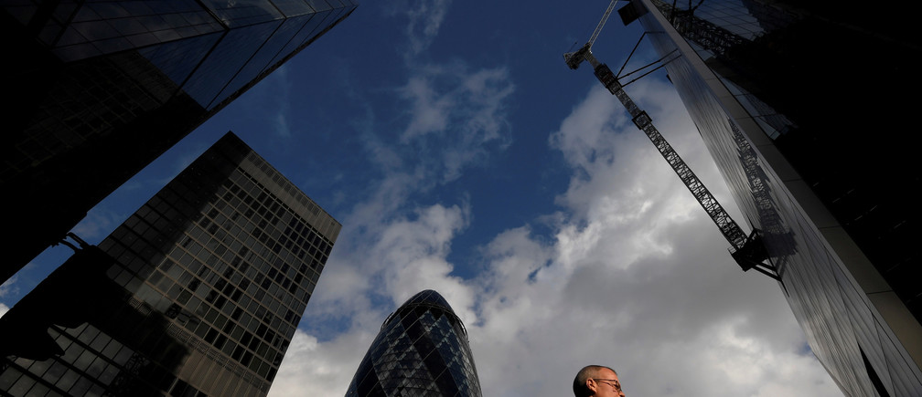 A worker walks past office skyscrapers in the City of London financial district, London, Britain, January 25, 2018. Picture taken January 25, 2018.  REUTERS/Toby Melville     TPX IMAGES OF THE DAY
