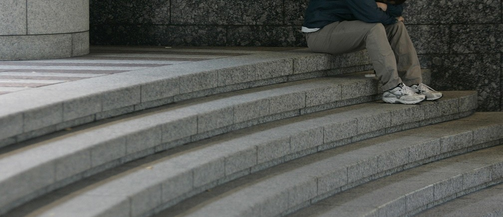 A man sits hunched over on a staircase in Tokyo November 17, 2008. Japan slid into its first recession in seven years in the third quarter as the financial crisis curbed demand for Japanese exports, and the economy minister and analysts offered little hope of a recovery until next year. REUTERS/Yuriko Nakao (JAPAN) - RTXAOF2