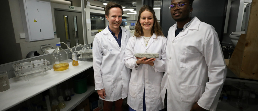 Researchers Dr. Dyllon Randall, Suzanne Lambert and Vukheta Mukhari stand with a bio-brick made  from urine at the University of Cape Town, in Cape Town, South Africa November 2, 2018. The odourless, grey prototype brick was grown in a mould in the lab over eight days and is the final product in a process that also produces fertilisers. REUTERS/Mike Hutchings - RC1D96876560