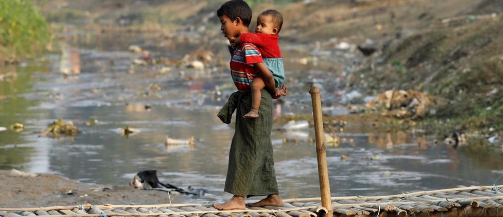 Two Rohingya refugee children on a bridge from no-man's land to Bangladesh, at the Bangladesh-Myanmar border.