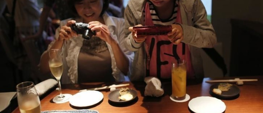 Yurika Miki (R) and her mother Yoshiko take photos of raw beef liver sashimi before eating them at a restaurant in Tokyo June 28, 2012. While Japan has a reputation as the home of sushi and sashimi, one item is about to be taken off the menu as Japan's government looks to ban the popular dish of raw liver in sashimi style. The dish, which consists of raw beef liver sliced up into bite sized chunks and then served with onions and sauce had become a popular dish across the country. Picture taken June 28, 2012. REUTERS/Toru Hanai (JAPAN - Tags: BUSINESS FOOD SOCIETY)