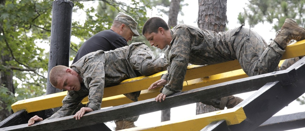 Captain Kristen Griest (R) participates in the Darby Queen obstacle course as part of the training at the Ranger Course on Ft. Benning Georgia, June 28, 2015.