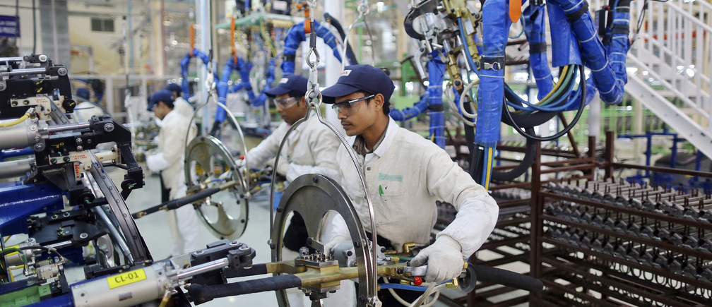 Employees work at the assembly line of the Honda Amaze car inside the company's manufacturing plant in Tapukara, in the desert Indian state of Rajasthan, February 24, 2014.