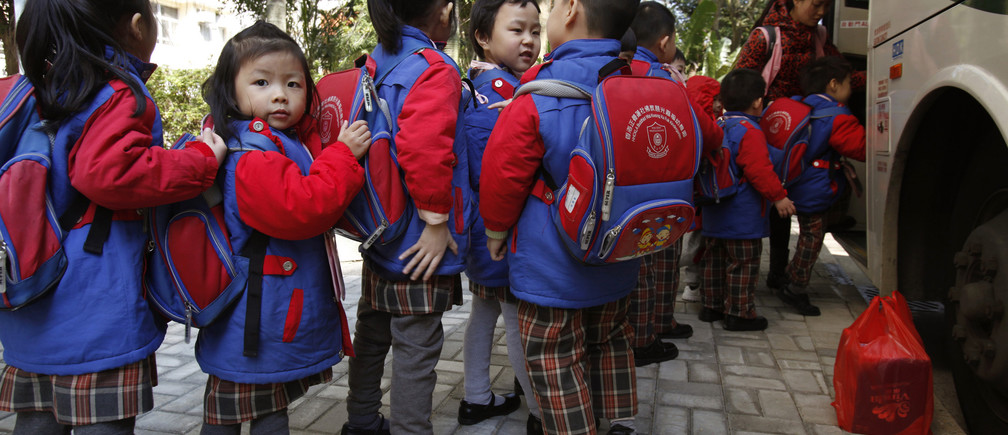 Students, who live in Shenzhen, line up for a school bus after school in Hong Kong December 19, 2013, before crossing the border back to mainland China. Every day, around 20,000 students are shuttled across the border from China, dressed in neat Hong Kong school uniforms and lugging their bags on trains and chartered buses. Roughly a quarter of births in Hong Kong between 2002 and 2012 - or more than 200,000 babies - were to families where both parents came from mainland China, who have rights to receive education in the territory. Picture taken December 19, 2013. To match story HONGKONG-EDUCATION/   REUTERS/Bobby Yip  (CHINA - Tags: EDUCATION POLITICS) - RTX189VR