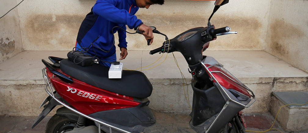 A boy prepares to recharge his electric scooter outside his home in Ahmedabad, India, December 30, 2018. Picture taken December 30, 2018. REUTERS/Amit Dave - RC192DD69CC0