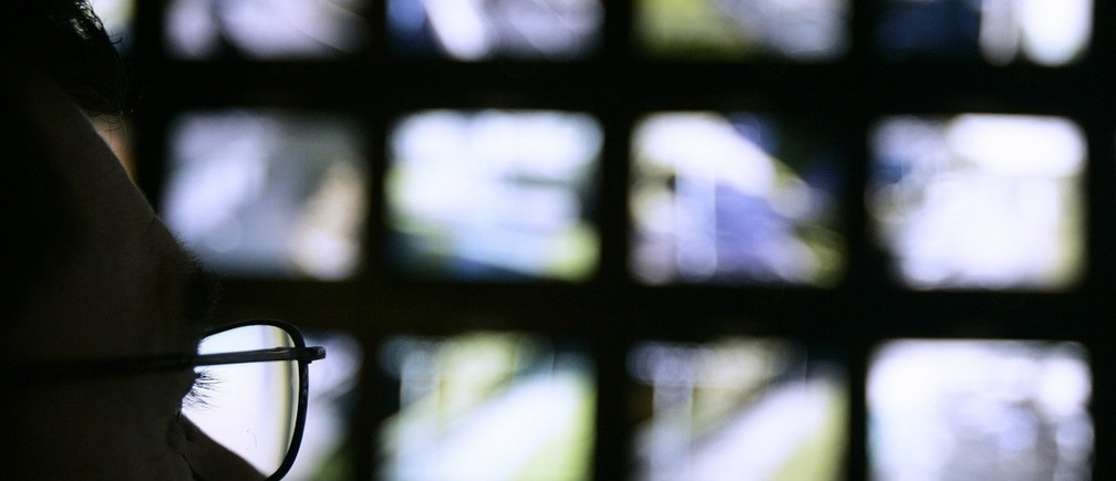 "A surveillance monitoring expert watches a bank of screens showing images from Edinburgh City Council's network of CCTV cameras in Edinburgh, Scotland November 2, 2006. Britain is becoming a surveillance society where individuals are filmed hundreds of times a day by security cameras and where firms ""data mine"" to build customer profiles, its information commissioner said on Thursday.   REUTERS/David Moir (BRITAIN) - RTR1IXMS"