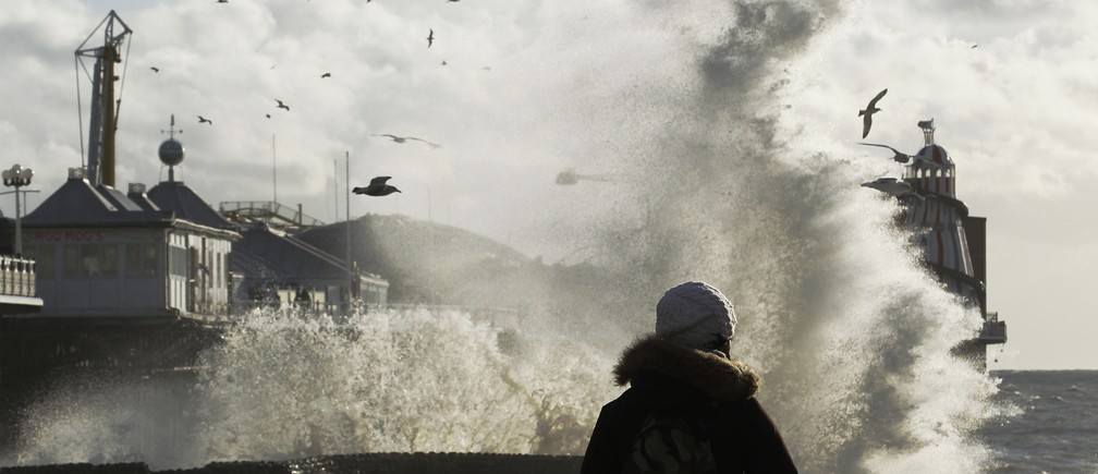 A woman watches giant waves crashing on the seafront by Brighton pier in southern England December 15, 2011. Britain is expecting to be battered by gale force winds and storms during the next 24 hours, according to the Met Office state forecasting agency.
