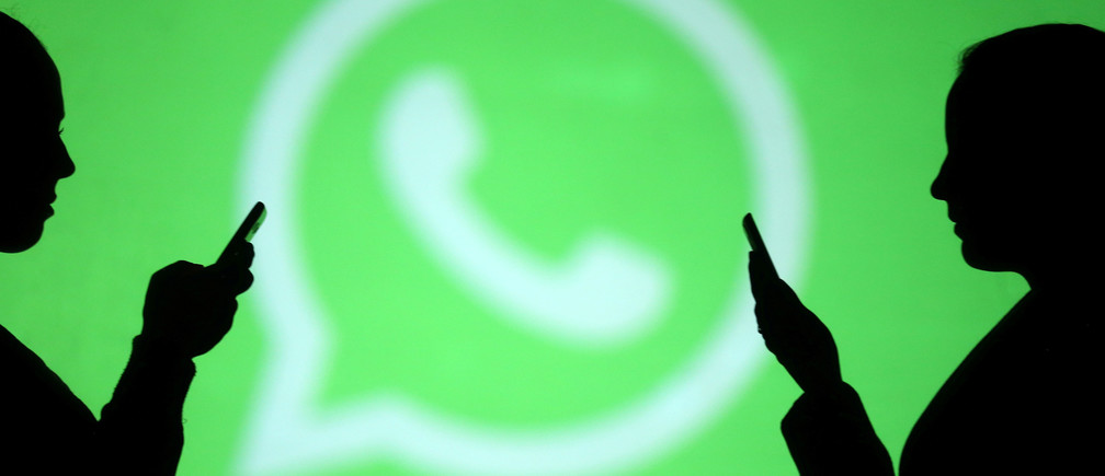Silhouettes of mobile users are seen next to a screen projection of Whatsapp logo in this picture illustration taken March 28, 2018.