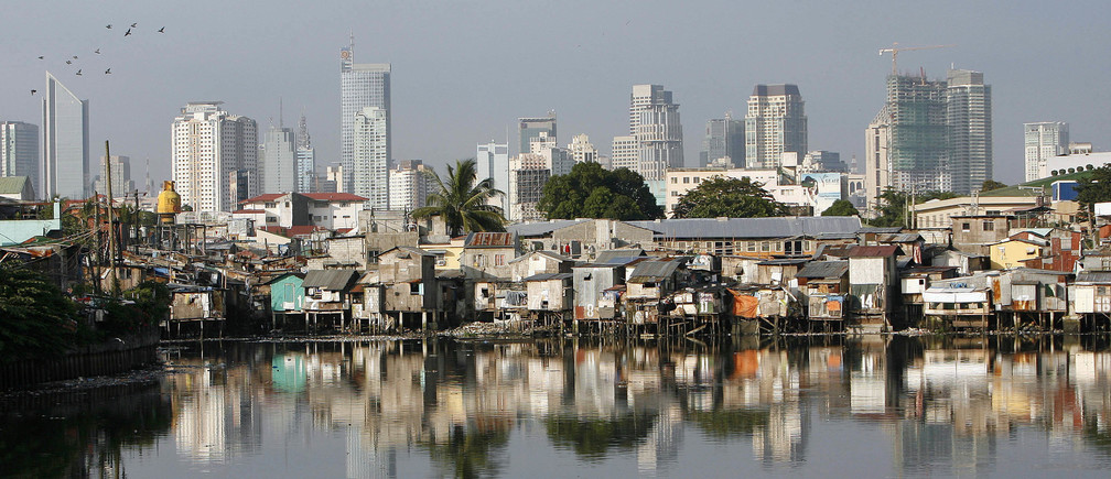 Slums are seen along a river with the skyline of Makati, Manila's financial district, in the background October 8, 2007. Developing countries in Asia are struggling to meet the UN-set millennium goals although the region is on course to cut extreme poverty, a report released on Monday showed. REUTERS/Cheryl Ravelo (PHILIPPINES) - GM1DWICSWHAA