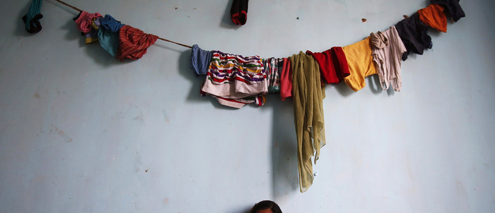 Sania, 25, sits underneath a line of clothes hung up to dry in the living room of their flat in an illegal building located next to the site of a building which collapsed last week, in Thane district on the outskirts of Mumbai April 10, 2013. A shortage of affordable housing in Indian cities has led to rampant illegal construction by developers using cheap materials and shoddy methods in order to offer low-cost homes to low-paid workers, paying bribes to officials to turn a blind eye. Despite several promises by the government to build affordable homes for India's poor in densely populated cities, the country's urban housing shortage is estimated at nearly 19 million households. That lack of affordable housing is especially acute in Mumbai, India's financial capital and home to some of the world's costliest real estate, where an estimated six out of every 10 people live in slums. Picture taken April 10, 2013. REUTERS/Vivek Prakash (INDIA - Tags: SOCIETY TPX IMAGES OF THE DAY) - GM1E94C05KW01