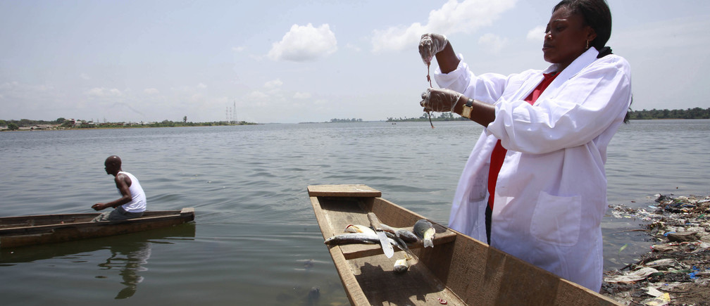 Dr. Celine Nobah (R) of the Association of Women Researchers in the Ivory Coast (AFEMC-CI) stands beside a canoe as she conducts research to ensure that fish in the lagoon Ebrie are safe for consumption, in Nbadon, Abidjan March 4, 2013. The association was formed to raise the profile of women working in scientific research in the Ivory Coast. It helps women raise funding for their projects and seeks to promote scientific research, a field dominated by men, as a viable career option among young women by helping them obtain scholarships. REUTERS/Thierry Gouegnon (IVORY COAST - Tags: SCIENCE TECHNOLOGY BUSINESS MARITIME) - GM1E9370LT601
