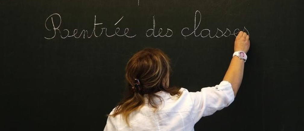 "A teacher writes the phrase ""Tuesday, September 1, 2015, start of the new school year"" on the blackboard before the arrival of French President Francois Hollande at the Groupe Le Marais primary school in Pouilly-sur-Serre, near Laon, northern France, September 1, 2015. REUTERS/Jacky Naegelen"
