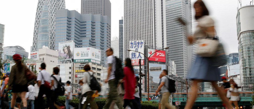 People cross a street in front of high-rise buildings in the Shinjuku district in Tokyo, Japan, September 29, 2016. Picture taken September 29, 2016. REUTERS/Toru Hanai - RTSQGL8