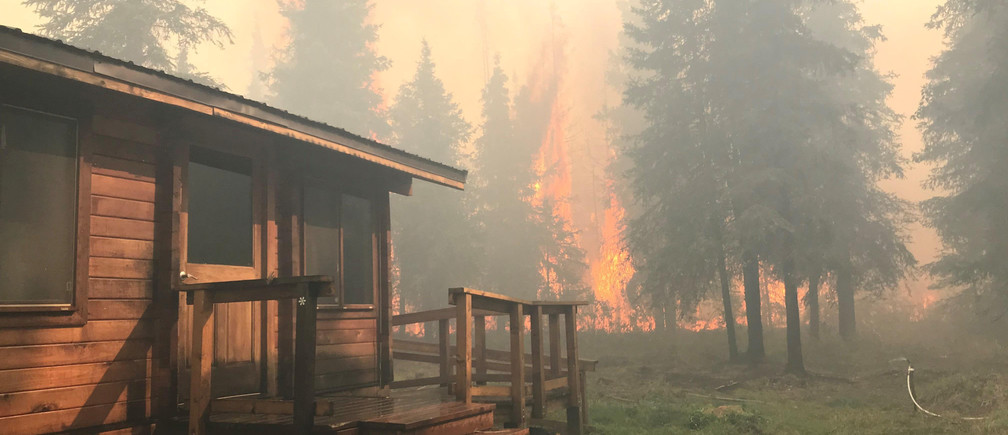 Firefighters from the Chugach National Forest work to protect the Romig Cabin on Juneau Lake from the Swan Lake Fire near Cooper Landing, Alaska, U.S. in this August 28, 2019 handout photo.   Chugach National Forest/Handout via REUTERS ATTENTION EDITORS - THIS IMAGE WAS PROVIDED BY A THIRD PARTY. - RC17D6156610