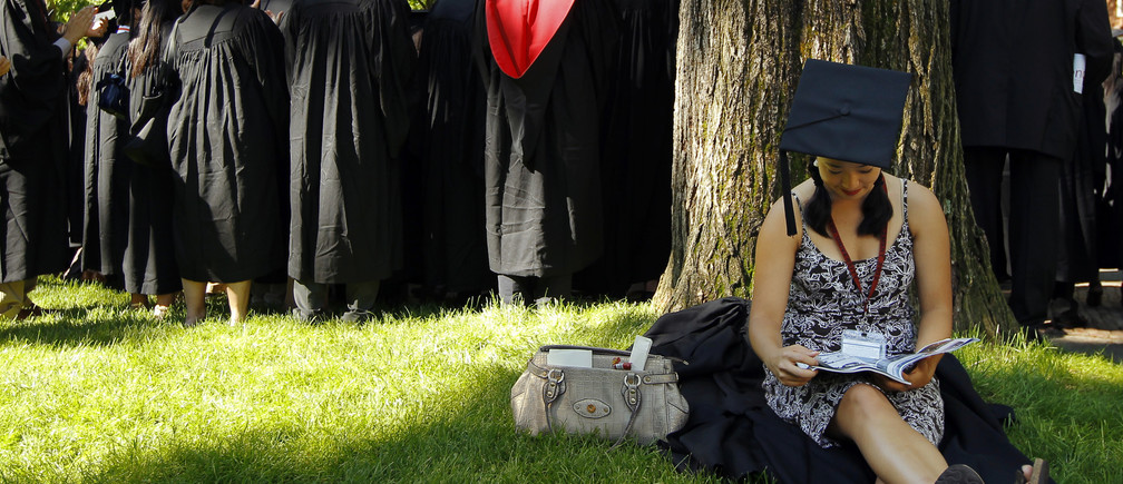 Graduating student Jennifer Lim sits in the shade before the start of the 361st Commencement Exercises at Harvard University in Cambridge, Massachusetts May 24, 2012.   REUTERS/Brian Snyder    (UNITED STATES - Tags: EDUCATION) - GM1E85P08GE01