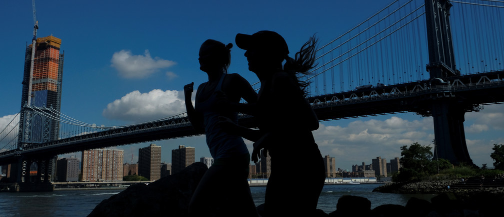Two women jog near Manhattan Bridge in Brooklyn, New York