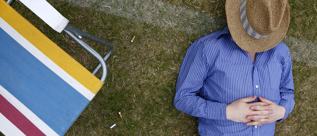 A man sleeps during the final of the Gold Cup British Open Polo Championship match between Ellerston and Loro Piana at Cowdray Park near Midhurst, southern England, July 20, 2008.   REUTERS/Luke MacGregor    (BRITAIN) - GM1E47L07MW01
