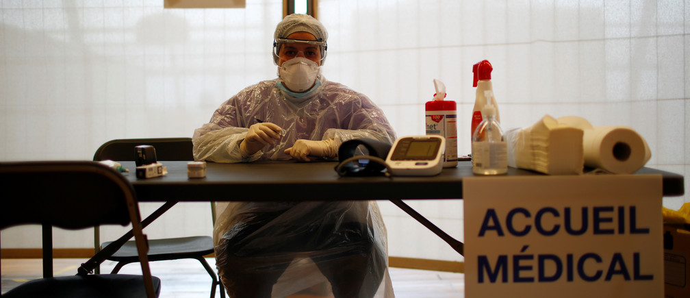 A member of the medical staff, wearing protective suit and face mask, works at an emergency COVID-19 center inside a gymnasium in Champigny-sur-Marne near Paris as the spread of the coronavirus disease continues in France, March 31, 2020. REUTERS/Gonzalo Fuentes - RC21VF9VD6Z6