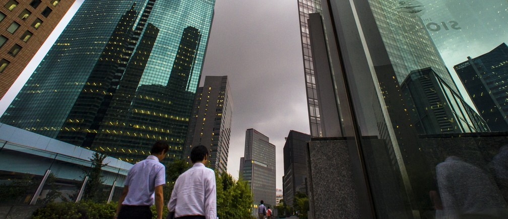 People walk in the shadows of office skyscrapers in a business district in Tokyo August 20, 2015.