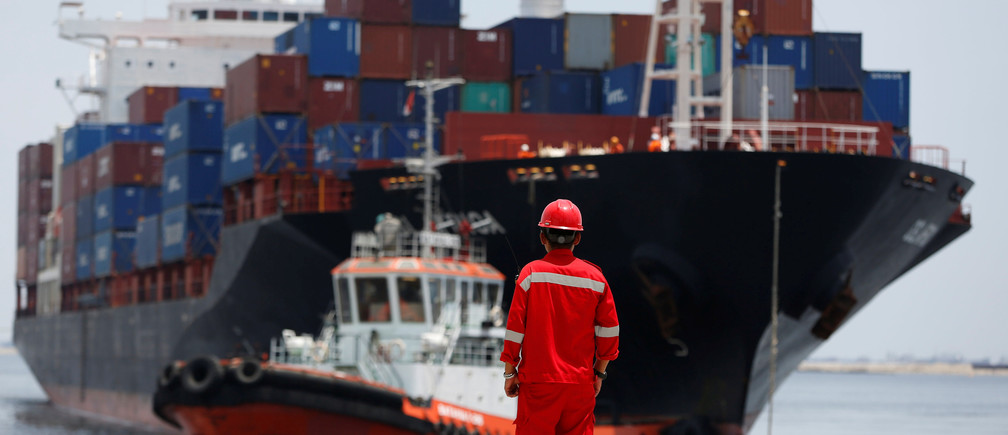 A port worker watches as a ship leaves the New Priok Container Terminal 1 in North Jakarta, Indonesia September 13, 2016