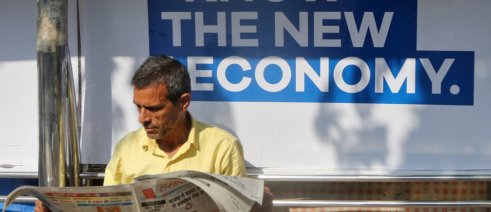 A man reads a newspaper as he waits for public transport at a bus stop in Mumbai, India, January 31, 2017.  REUTERS/Shailesh Andrade - RTX2YXLC