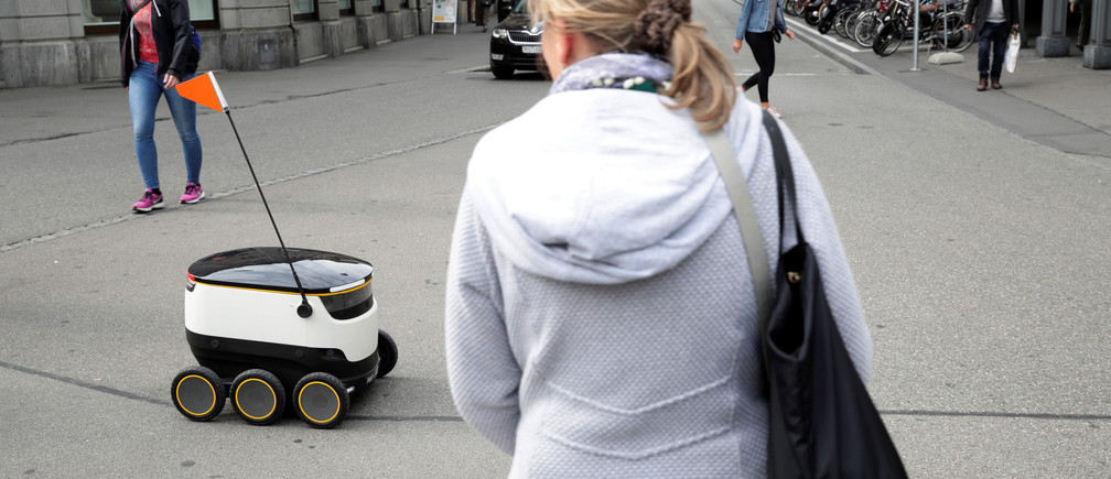 A Swiss Post self-driving delivery robot, capable of carrying up to 10 kg over 1 kilometer, with a speed up to 6 km/h, delivers a package from the department store Jelmoli during a press presentation for the start of the service in Zurich, Switzerland, September 8, 2017. REUTERS/Moritz Hager - RC1D9B779E30