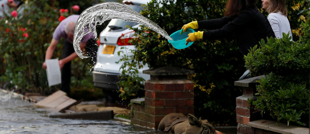 A woman uses a bowl to clear water from her drive to prevent rising flood water from entering her house in the Sale area of Manchester, Britain, July 31, 2019. REUTERS/Phil Noble - RC1C51E0EF70