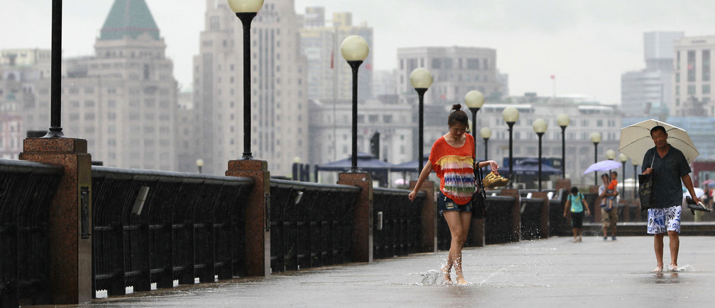 A woman walks along the flooded banks of the Huangpu River, Shanghai.