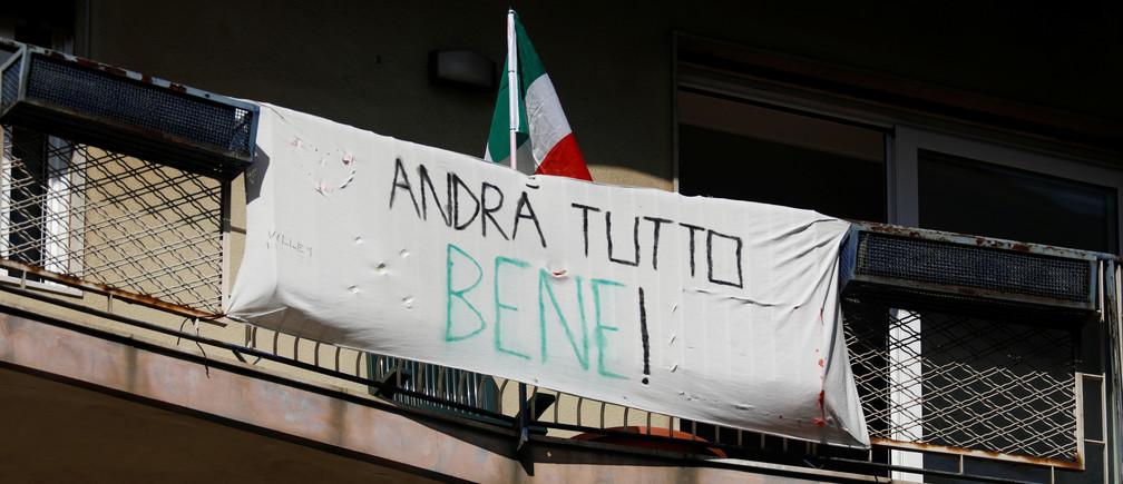 """Una pancarta cuelga en un balcón, el Domingo de Ramos, tras el brote de la enfermedad coronavirus (COVID-19), en Catania, Italia, el 5 de abril de 2020. La pancarta dice: """"¡Todo va a estar bien!"""""""