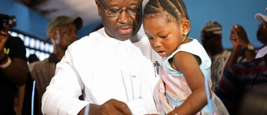 Julius Maada Bio, the presidential candidate for the Sierra Leone People's Party (SLPP), carries his daughter as he casts his vote during a presidential run-off in Freetown, Sierra Leone March 31, 2018. REUTERS/Olivia Acland - RC12F86D4000